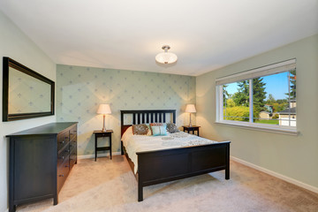 Traditionally furnished bedroom with black furniture and carpet floor.