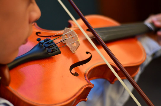 Child playing a violin. Blur style background.