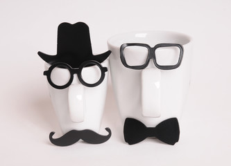 Two coffee cups in mans image. Hipster style, glasses, mustache, hat, bow tie
