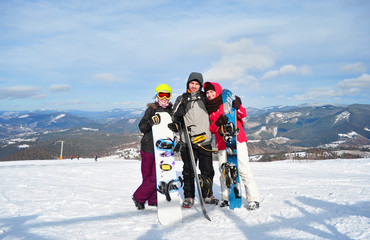 Two girls and a boy standing, smiling and holding snowboards on the background of the Carpathian mountains on a sunny winter day.