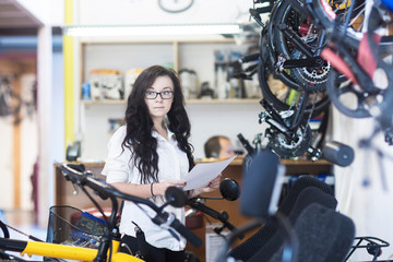Woman in bicycle shop holding paperwork