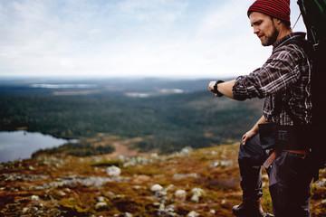 Hiker checking time on cliff top, Keimiotunturi, Lapland, Finland