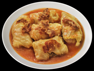 Plateful Of Cabbage Rolls Stuffed With Minced Meat Cooked In Tomato Sauce With Smoked Pork Ham Slices Isolated On Black Background