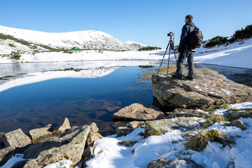 Photographer taking photos of beautiful landscape in the mountain lake. Winter lake. Travel inspiration and motivation, beautiful landscape.