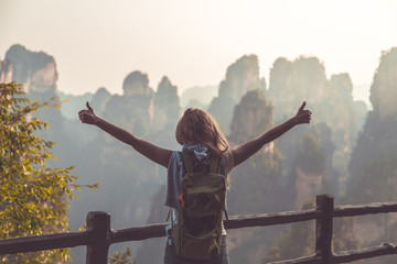 Young woman standing on top of the mountain with view over scenic area of Wulingyuan Park, raising her hands with thumbs up. Success conpect.
