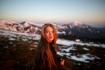 Young woman in long mystical dress looking into the sun stands on the top of the mountain. Woman on the background of snow winter and mounts. Travel inspiration and motivation, beautiful landscape.