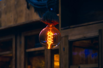 Hanging decorative filament light bulb in a dim atmosphere