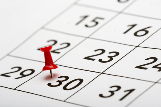 Pin on the date 30. The thirtieth day of the month is marked with a red thumbtack. Last days of the month Focus point on the red pin.