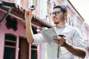 Tourism and Technology. Young man traveler with a camera Action card and phone in his hands.