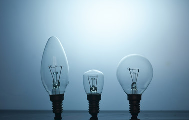 Three incandescent light bulb on a blue background. Variety of forms of incandescent light bulbs.