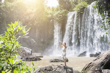 Cambodia, Nationalpark Phnom Kulen, young woman taking selfie with smartphone in front of waterfalls