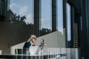 Businesswoman at desk looking at figurine