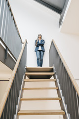Confident businesswoman with long grey hair standing on top of stairs
