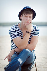 Portrait of a young man on the beach dressed in a nautical style.