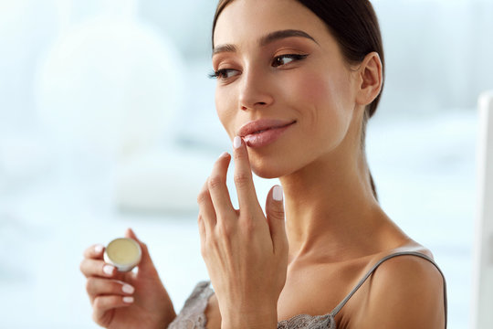 Lips Skin Care. Woman With Beauty Face Applying Lip Balm On