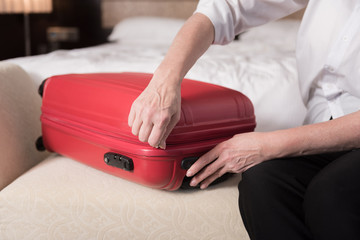 Red modern valise lying on the sofa