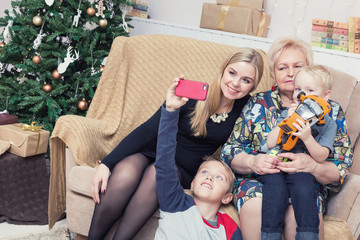 Happy family taking pictures with smartphone on Chistmas decorations