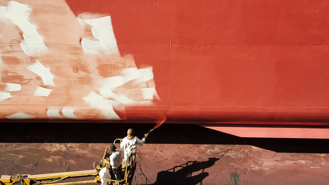 men painting ship hull