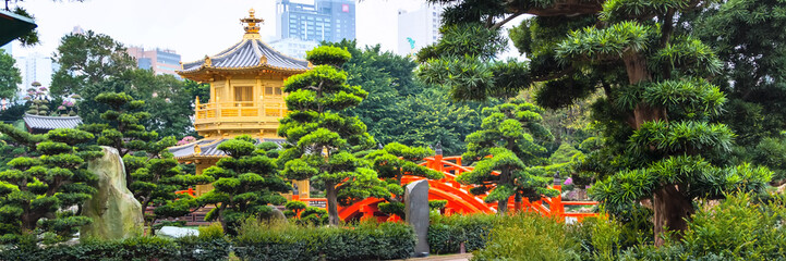 Traditional chinese pavilion in public Nan Lian Garden, Hong Kong, China and bonsai trees panorama Wall mural