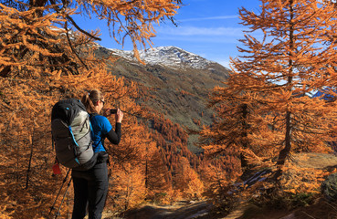Fotomurales - Female hiker photographing the warm autumn colors in the Claree valley, France.
