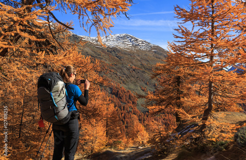 Fotomurales Female hiker photographing the warm autumn colors in the Claree valley, France.