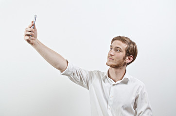 Young Adult Man in White Shirt Takes a Selfie with His Smart Phone