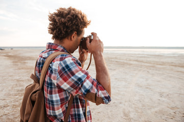 African man with backpack taking pictures on the beach