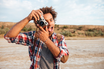 Cheerful man taking pictures and having fun on the beach