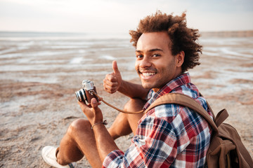 Happy man taking photos and showing thumbs up on beach