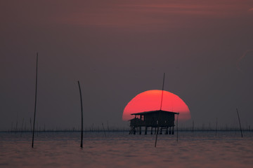 Hut in the sea at sunset