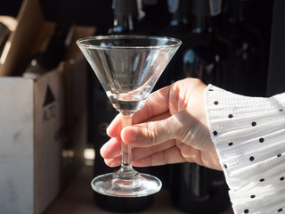 A hand holding an empty cocktail glass