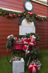 Christmas gifts inside sleigh, with flowers and decorated tree.