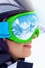 Portrait of snowboarder woman on  beautiful landscape background.A Mountain Range Reflected in the Ski Mask
