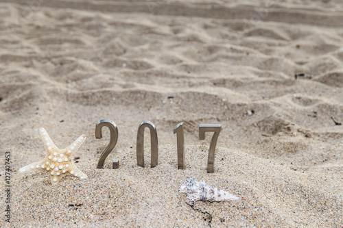 happy year 20172017 year metal sign and shellfish on sandy beach in florida