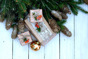 gift box with tree branches and cones on wooden background