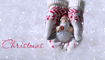 Christmas toy Santa Claus in the hands dressed in gloves on a white background