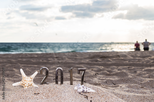 new year resolution2017 metal number sign and shellfish with a couple looking at sunrise