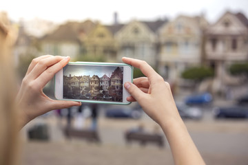 a tourist taking pictures of Painted Ladies with a smart phone,