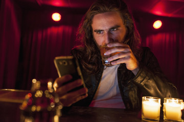 Young man checking his cell phone while at a nightclub