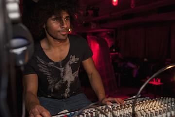 Young man playing DJ mixer in nightclub
