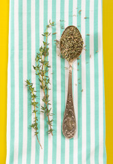 Antique teaspoon with dried and fresh thyme on folded towel, with yellow background.