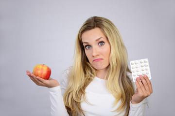 Junge Frau mit Apfel und Tabletten
