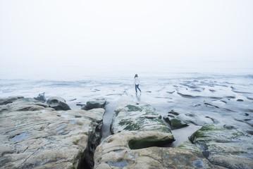 Woman standing on rocks, Kamakura Beach, Japan, East Asia