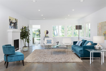 Beautiful and large living room interior with hardwood floors and vaulted ceiling in new luxury home. View of Kitchen, entryway, and second story loft style area.