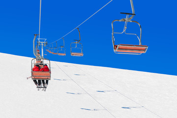 Chairlifts transport skiers and snowboarders up slope at ski resort
