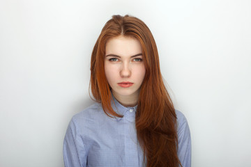 Young serious angry redhead beautiful woman in shirt portrait on a white background