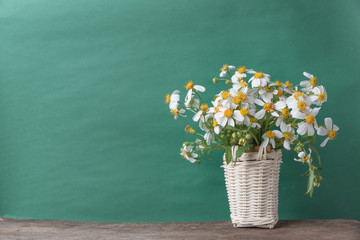 white flowers in basket on wooden table with old green background, vintage tone.