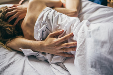 beautiful couple lying together on the bed. male hand closeup