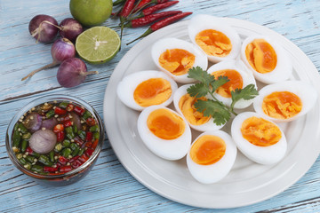 Boiled eggs and fish sauce with chili lemon and shallots on blue wood floor. Thai food