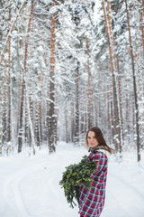 girl keeps fir branches in the winter forest